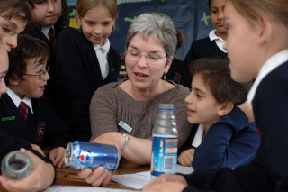 A photo of a woman teaching school children about recycling